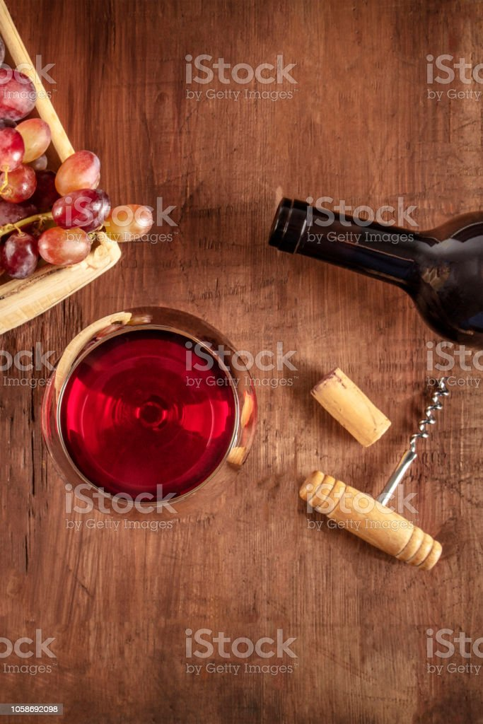 An overhead photo of a glass of red wine with a bottle, grapes, a vintage corkscew and a cork, shot from above on a dark rustic wooden background with a place for text stock photo