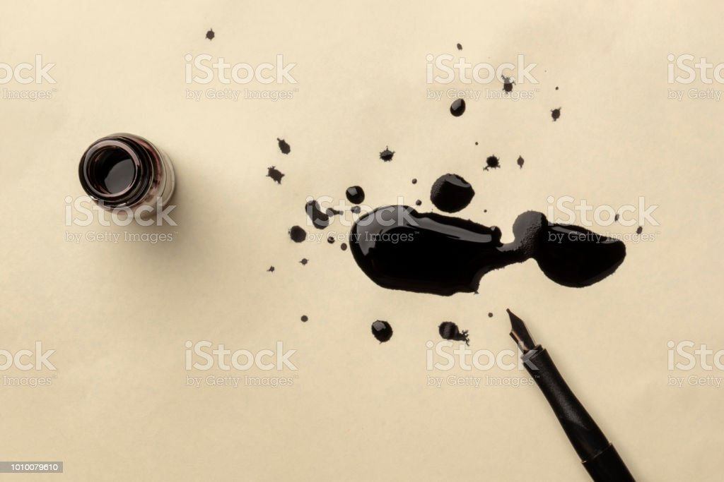 An overhead photo of an ink well with drops of ink and a nib pen, with copy space royalty-free stock photo