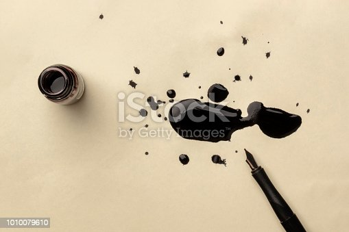 An overhead photo of an ink well with drops of ink on a textured off-white paper, with a nib pen, with copy space