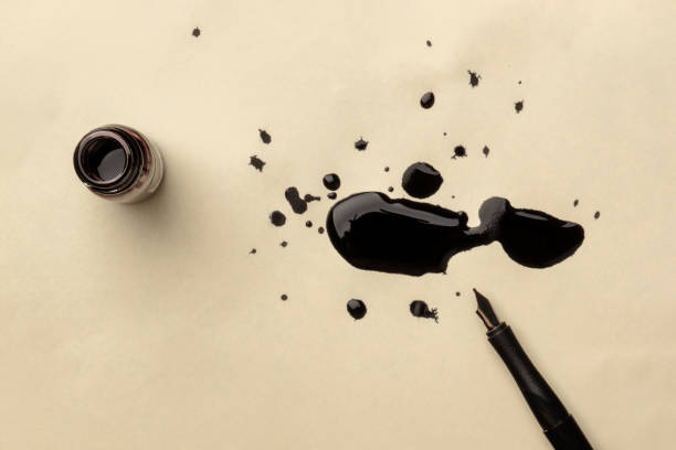 an overhead photo of an ink well with drops of ink and a nib pen, with copy space - ink stock pictures, royalty-free photos & images