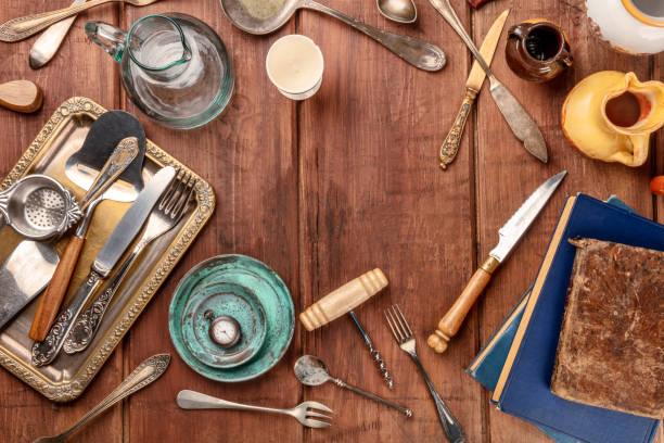 ein overhead foto von vielen vintage küche objekte und besteck ein altes restaurant, flohmarkt und gebrauchte bücher auf einem hölzernen hintergrund mit textfreiraum - kücheneinrichtung nostalgisch stock-fotos und bilder