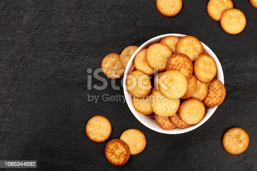 An overhead photo of salt crackers in a bowl, shot from the top on a dark background with copy space
