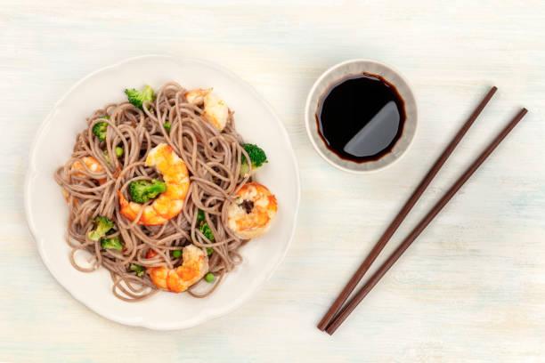 een van de foto's voor soba, boekweit noodles, garnalen en groenten, met stokjes en sojasaus, een overhead schot van bovenaf op een lichte achtergrond - sobanoedels stockfoto's en -beelden
