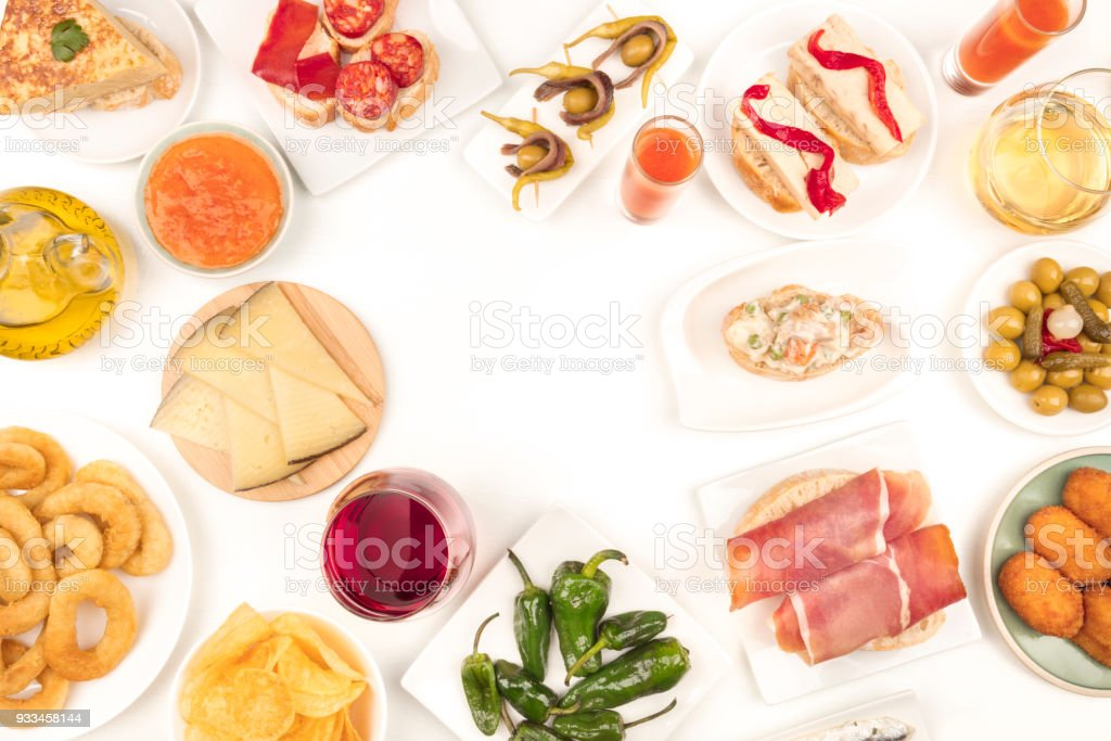 An overhead photo of Spanish tapas, forming frame on white with place for text stock photo