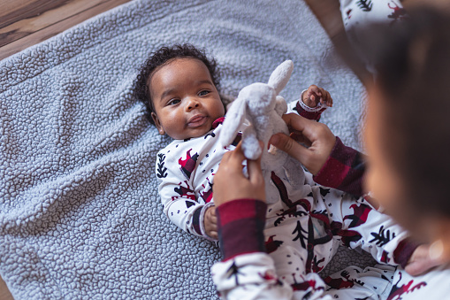 A sister of elementary school age is playing with her baby sister on Christmas Day. The baby girl is wearing a Christmas onesie and smiling up at her sister. Her sister is playfully holding a stuffed bunny over her face.