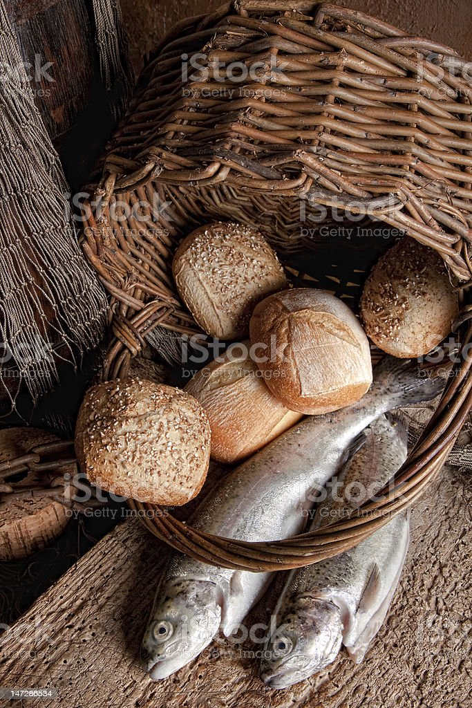 An overturned basket of bread loaves and two uncooked fish stock photo