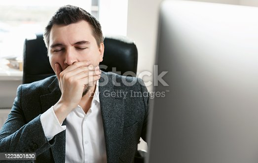 921587490 istock photo An overworked employee works on a desktop computer. Tired businessman or office worker yawns and falls asleep at the workplace. Sales manager, financial analyst or IT specialist, freelancer. 1223801830