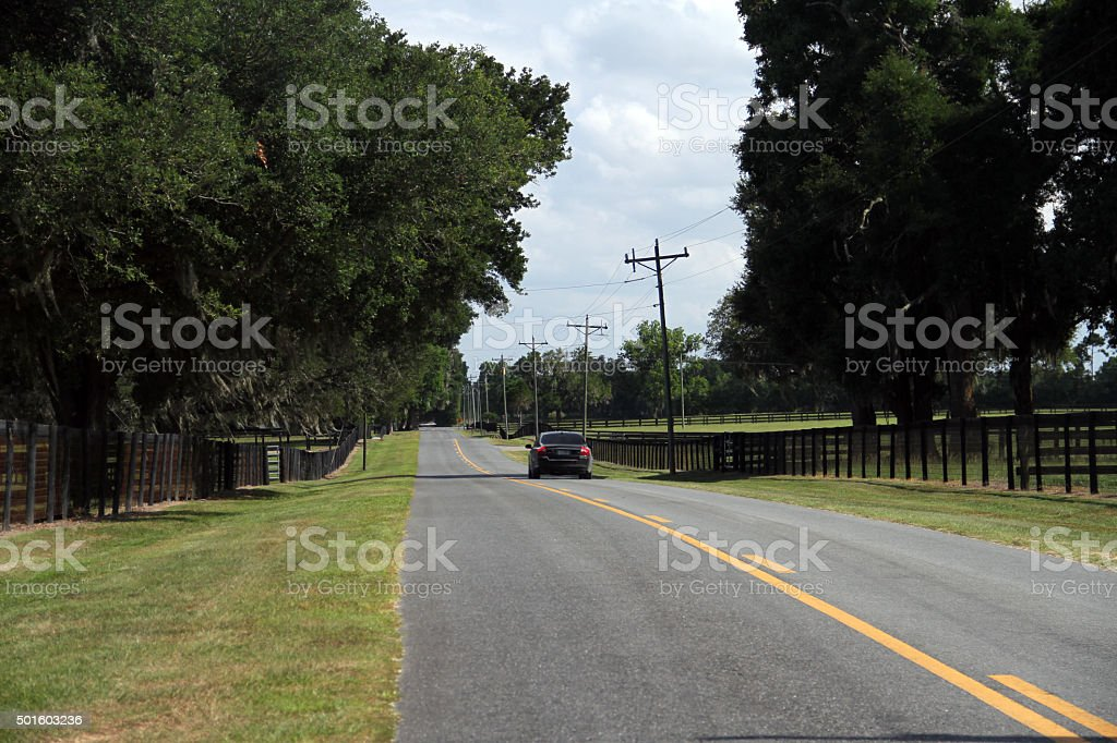 An road with a car yellow lines and beautiful sky stock photo