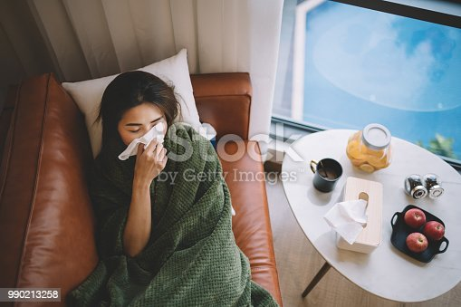 an sick asian chinese female lying on sofa in living room covered with blanket and wiping nose with tissue paper
