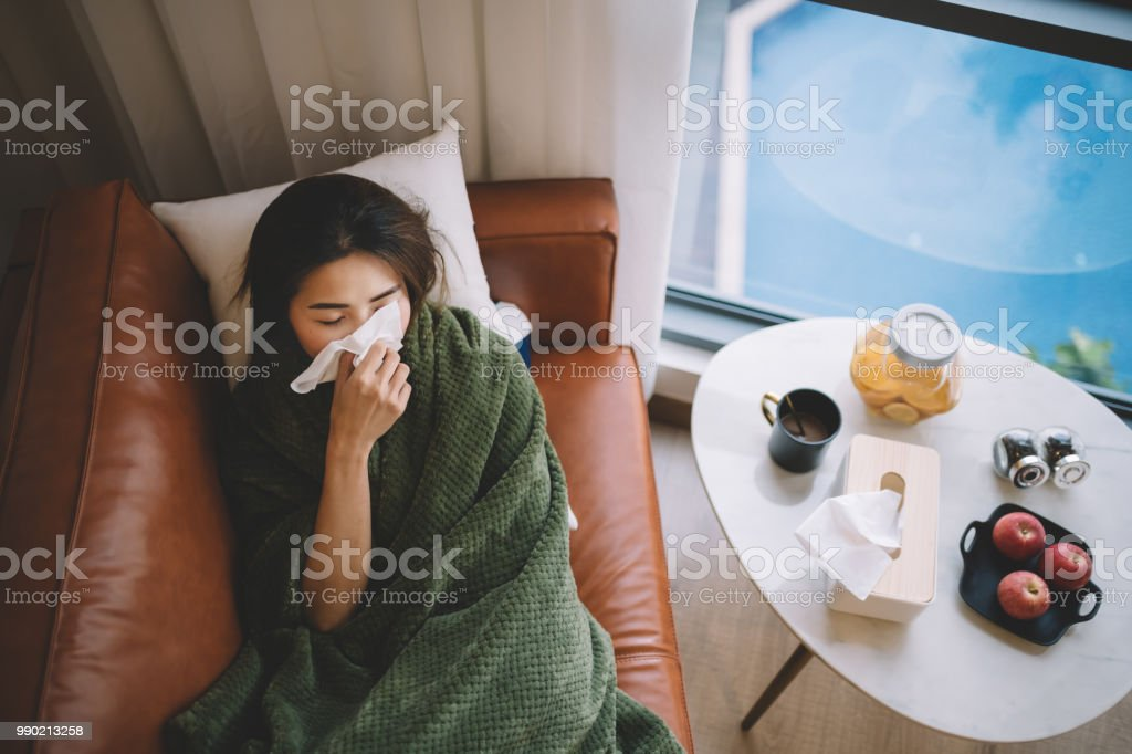 an sick asian chinese female lying on sofa in living room covered with blanket and wiping nose with tissue paper stock photo