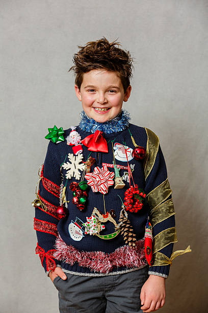 An ugly Christmas Sweater A child wearing a homemade ugly Christmas sweater using ornaments, ribbons and garland on a gray backdrop. ugliness stock pictures, royalty-free photos & images