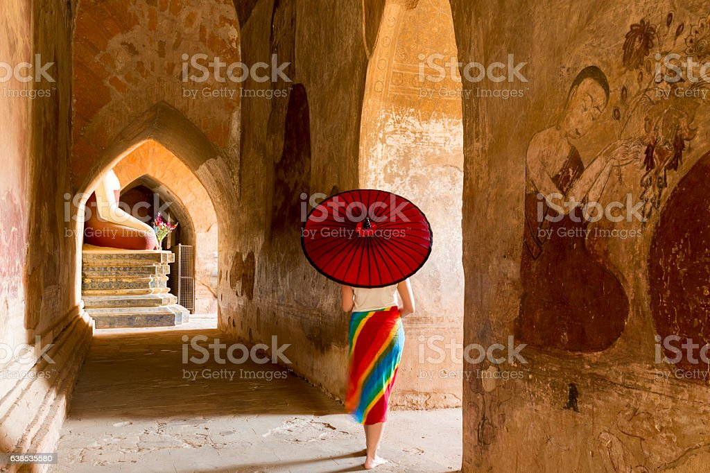An umbrella woman walks in the temple stock photo