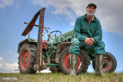 A farmer sits on the front wheel of his old tractor and looks thoughtfully out over his mown meadow. What will bring the future of agriculture?