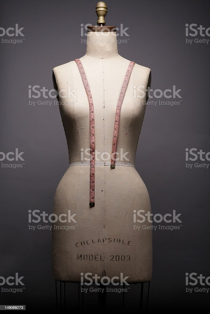 An undressed mannequin with a tape measure draped on it stock photo
