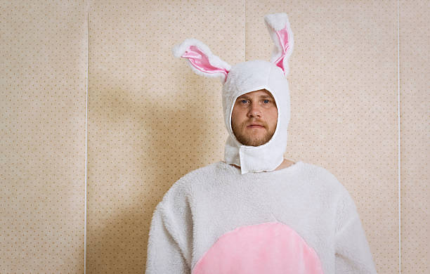 an unhappy man, dressed in a bunny outfit - easter bunny stock photos and pictures