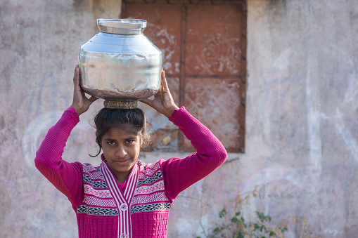TIKAMGARH, MADHYA PRADESH, INDIA - JANUARY 23, 2021: An unidentified indian village girl carry water on their heads in traditional pots from well, An Indian rural scene.