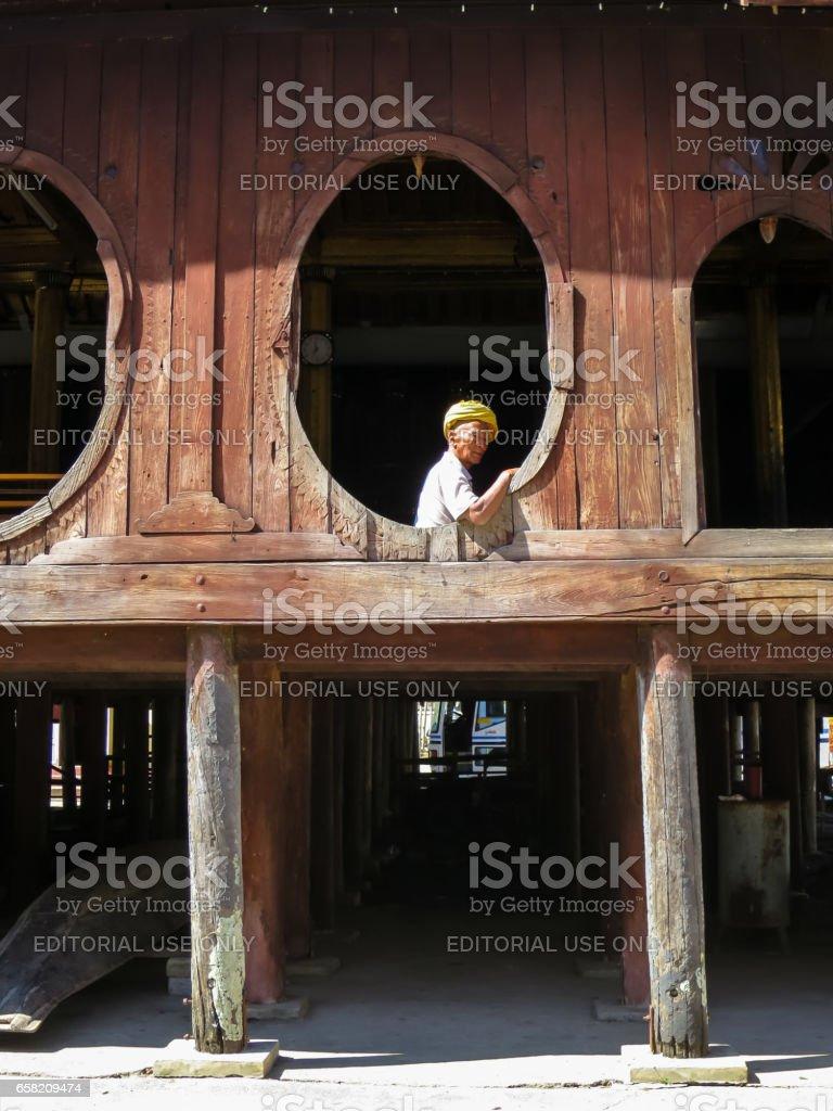 Nyaungshwe, Myanmar - January 24, 2015: An unidentified local old man wearing yellow turban looking out the unique oval window of Shwe Yaunghwe Kyaung monastery, Inle Lake, Nyaung Shwe, Myanmar. stock photo