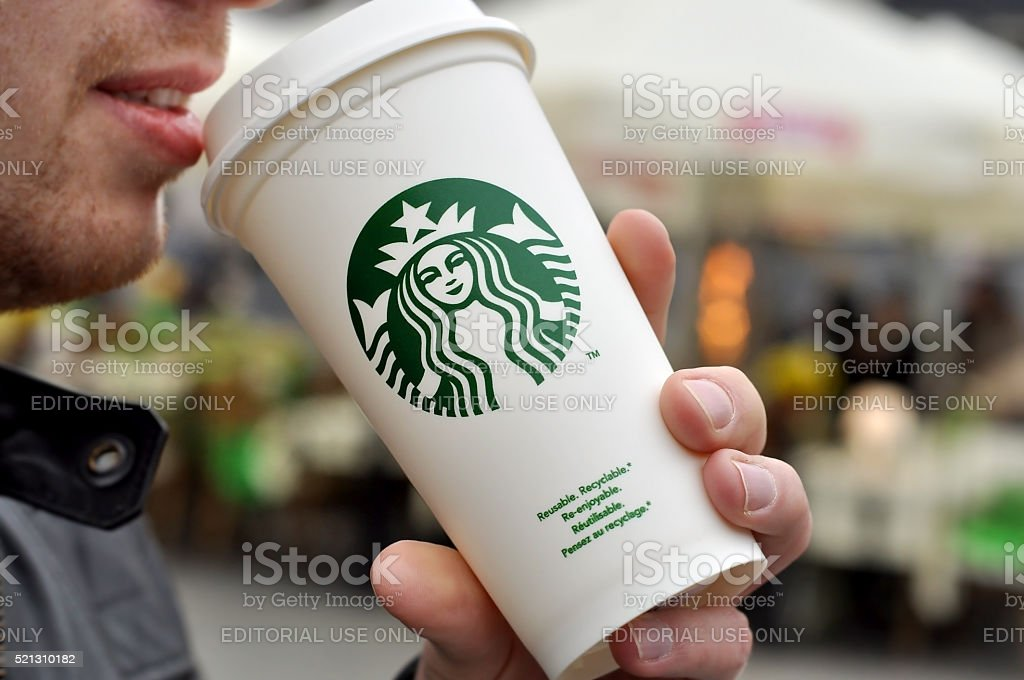 An Unidentified man holding a cup of beverage stock photo