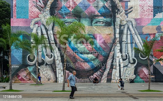"istock An unidentified man walks across the famous Olympic Boulevard of Rio de Janeiro with art mural called ""Etnias"" (Ethnicities) in the background 1218484125"