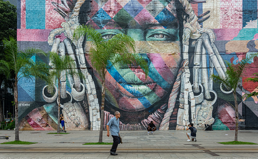 Rio de Janeiro, Brazil - January 3, 2020: An unidentified man walks across the famous Olympic Boulevard in the Port Zone of Rio de Janeiro with art mural called \
