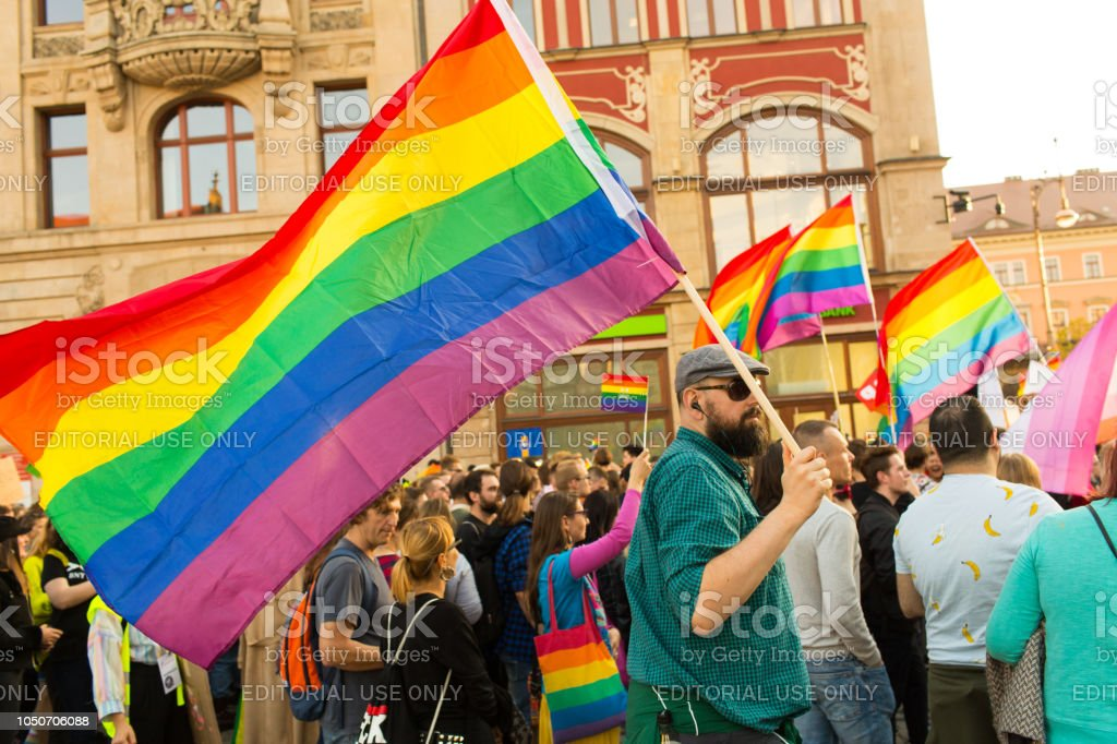 An unidentified man with a big rainbow flag during the LGBT parade stock photo