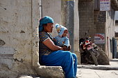 Jomsom, Mustang / Nepal - August 21, 2014: An unidentified Nepalese woman with a small child on her knees sits against the wall of a house on Jomsom Street. Nepal.