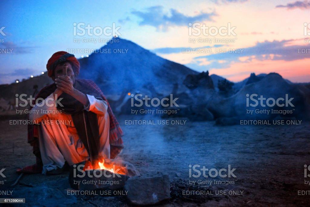 An unidentified Rajasthani man sitting near the temporary fire arrangement at Pushkar camel fair. stock photo