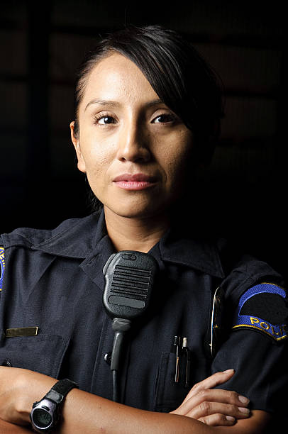 An uniformed female police officer with her arms folded a female hispanic police officer with her arms crossed in the night.  police uniform stock pictures, royalty-free photos & images