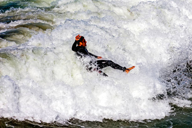 An unknown surfer falls into the water. stock photo
