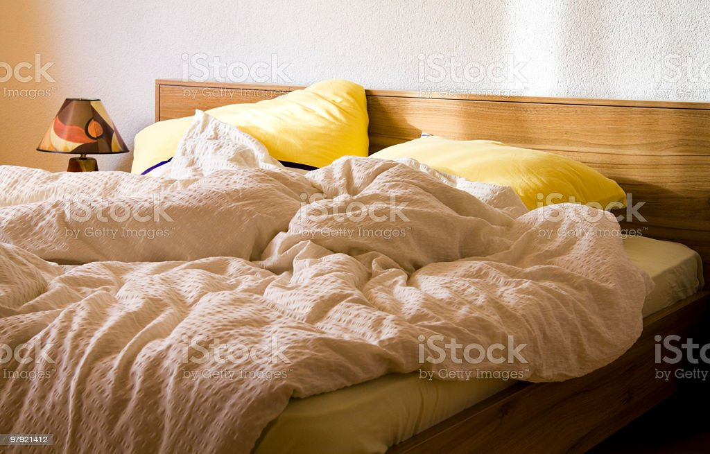 An unmade bed with yellow pillows in the morning royalty-free stock photo