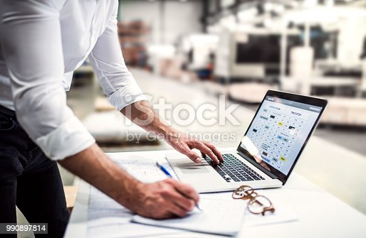 An unrecognizable industrial man engineer in white shirt working with laptop in a factory.