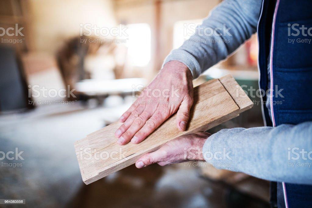 Um trabalhador homem irreconhecível na oficina de carpintaria, trabalhando com madeira. - Foto de stock de Adulto royalty-free