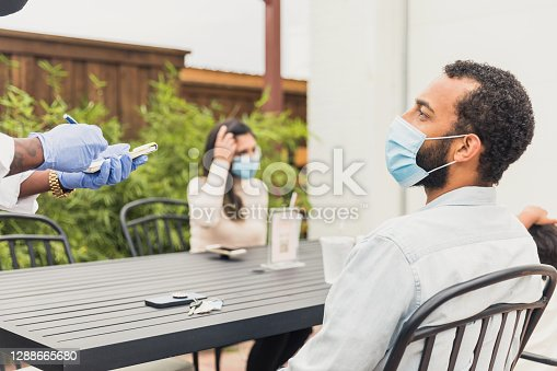 istock An unrecognizable waiter takes customer's order 1288665680
