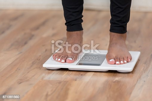 istock An unrecognizable woman stands on a bathroom scale 871381560
