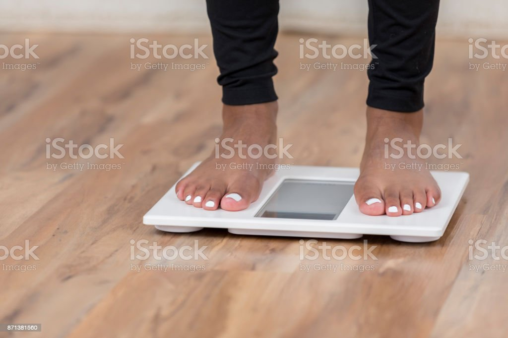 An unrecognizable woman stands on a bathroom scale stock photo