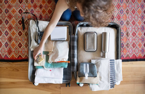 An unrecognizable young teenage girl packing for a holiday at home. Top view. stock photo