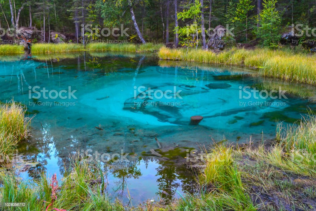 An unusual magical and mysterious geyser lake of turquoise color in...