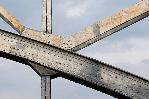 An up close image of the beams holding up a steel bridge Detail of steel bridge in front of blue sky girder stock pictures, royalty-free photos & images