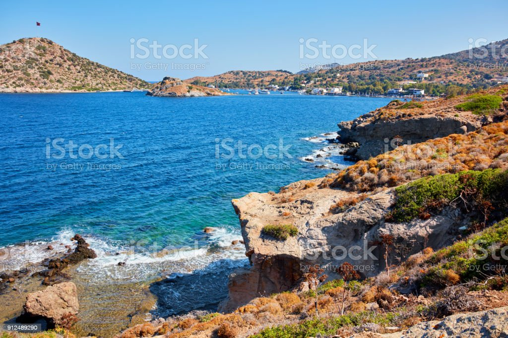 an up high view of Bodrum Gumusluk (Myndos) bay in Turke including cliffs, the rabbit island and the flag island. stock photo