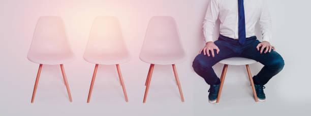 eine aufgeregt und gestresste mann gekleidet in ein hemd und krawatte sitzt auf einem stuhl in einem wartezimmer. - rot bekümmerte möbel stock-fotos und bilder