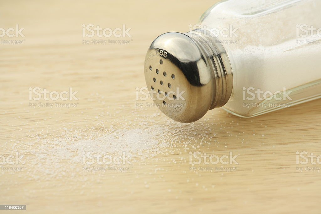 An upturned salt shaker on a table stock photo