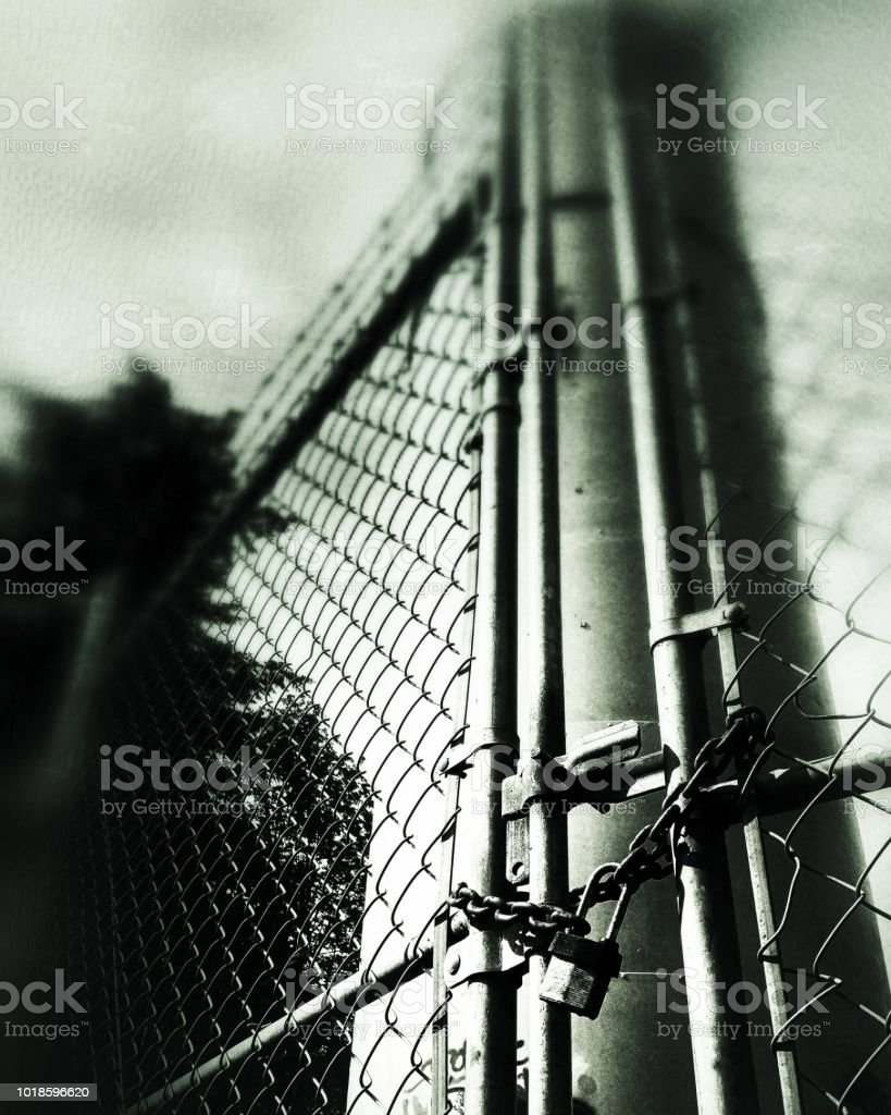 An upward angle looking through a locked chain link fence stock photo