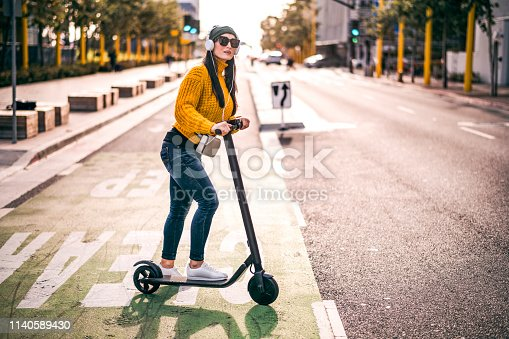 A modern woman listening to music over the headphones trying to merge into the traffic in the city street.