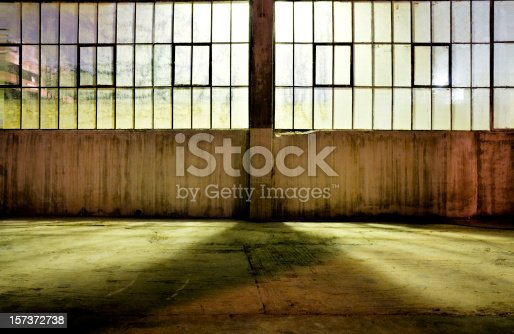 Inside an old warehouse at night. Looking towards backlit windows.