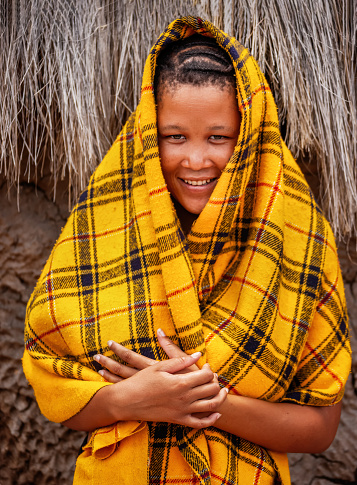 an young bushman girl from Central Kalahari, village New Xade in Botswana, in front of  a blanket her shack