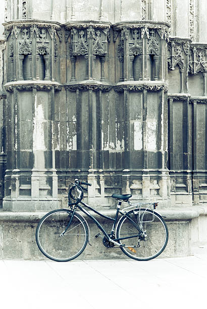 anachronistic bicycle leaning on the facade of a cathedral anachronistic stock pictures, royalty-free photos & images
