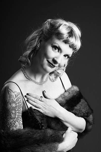 B&W anachronistic portrait in 1940s movie style. Vertical B&W studio glamour portrait in 1940s style but with arm tattoo. anachronistic stock pictures, royalty-free photos & images