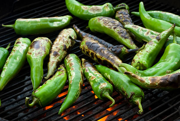anaheim chilis over fire - green chilli pepper stock photos and pictures