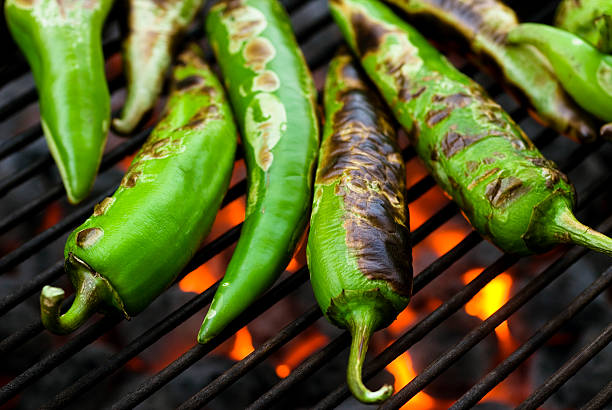 anaheim chilis roasting macro - green chilli pepper stock photos and pictures