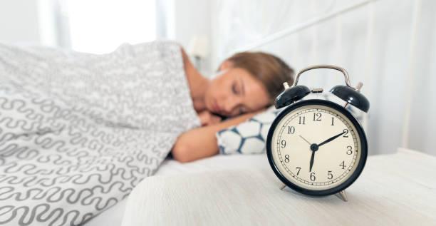 analoge wecker. frau schläft im bett - verwandlungskissen stock-fotos und bilder